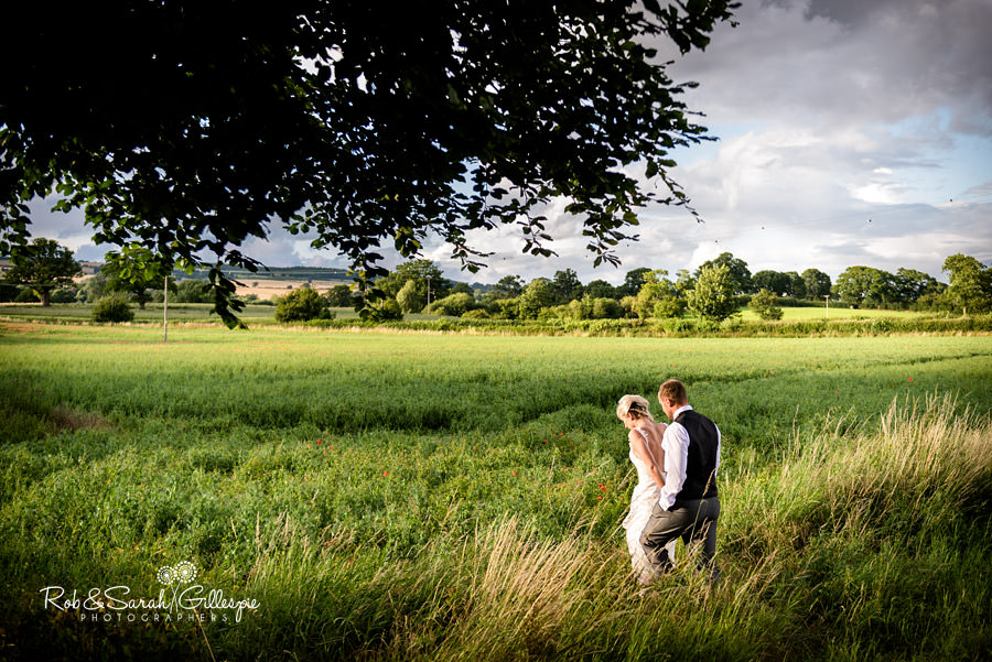 Bride and groom walk together in field at Delbury Hall with amazing evening light