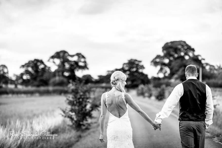 Bride and groom walking together in Delbury Hall grounds