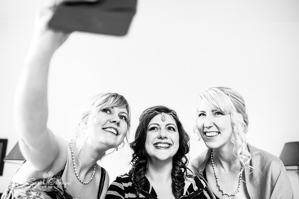 Bride and two bridesmaids smile for selfie photo