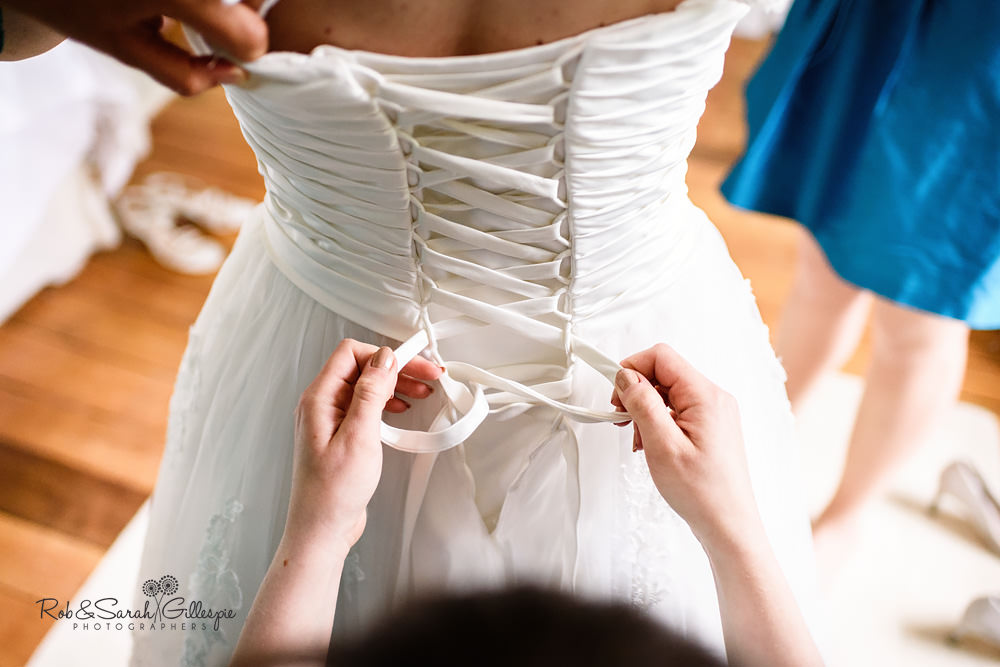 Bride's wedding dress being fastened from the back