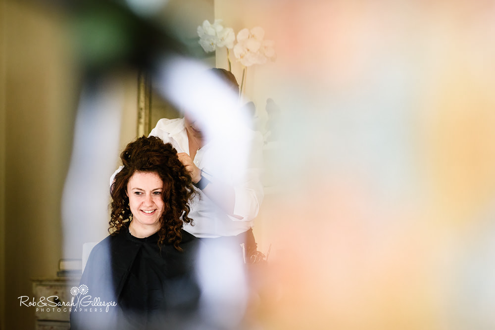 Photo of bride having hair styled