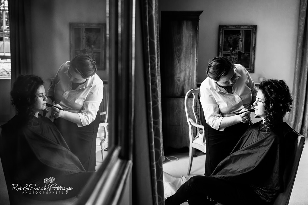 Bride having makeup applied, with reflection of her in a picture frame on the wall