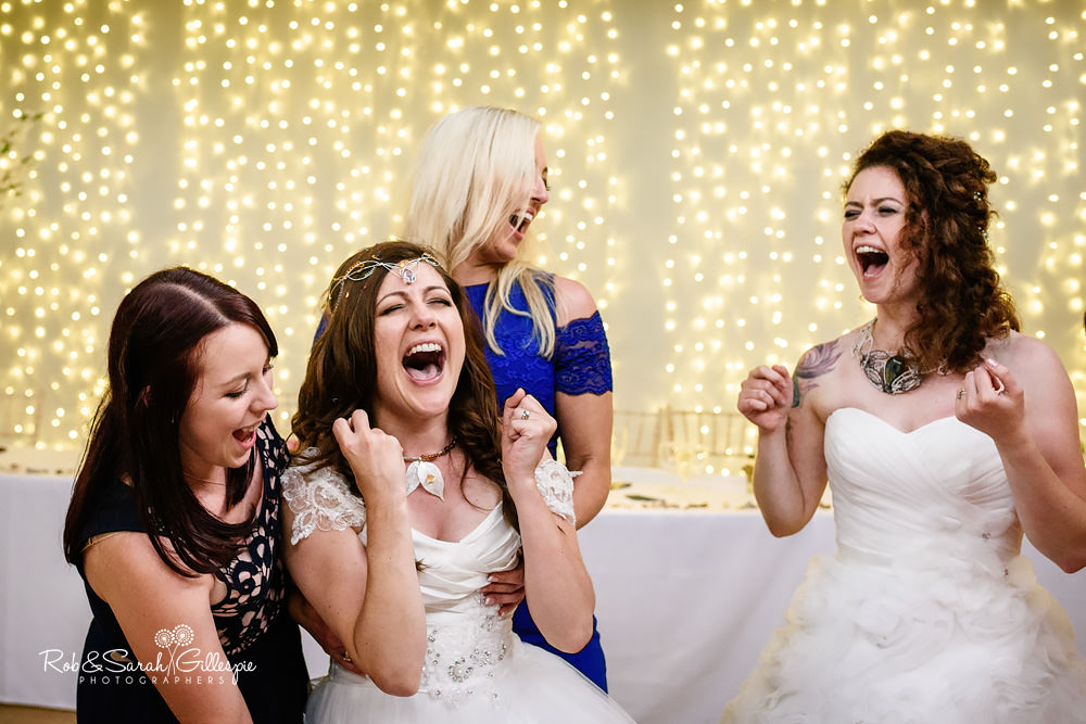 Brides singing with friends at same-sex wedding reception
