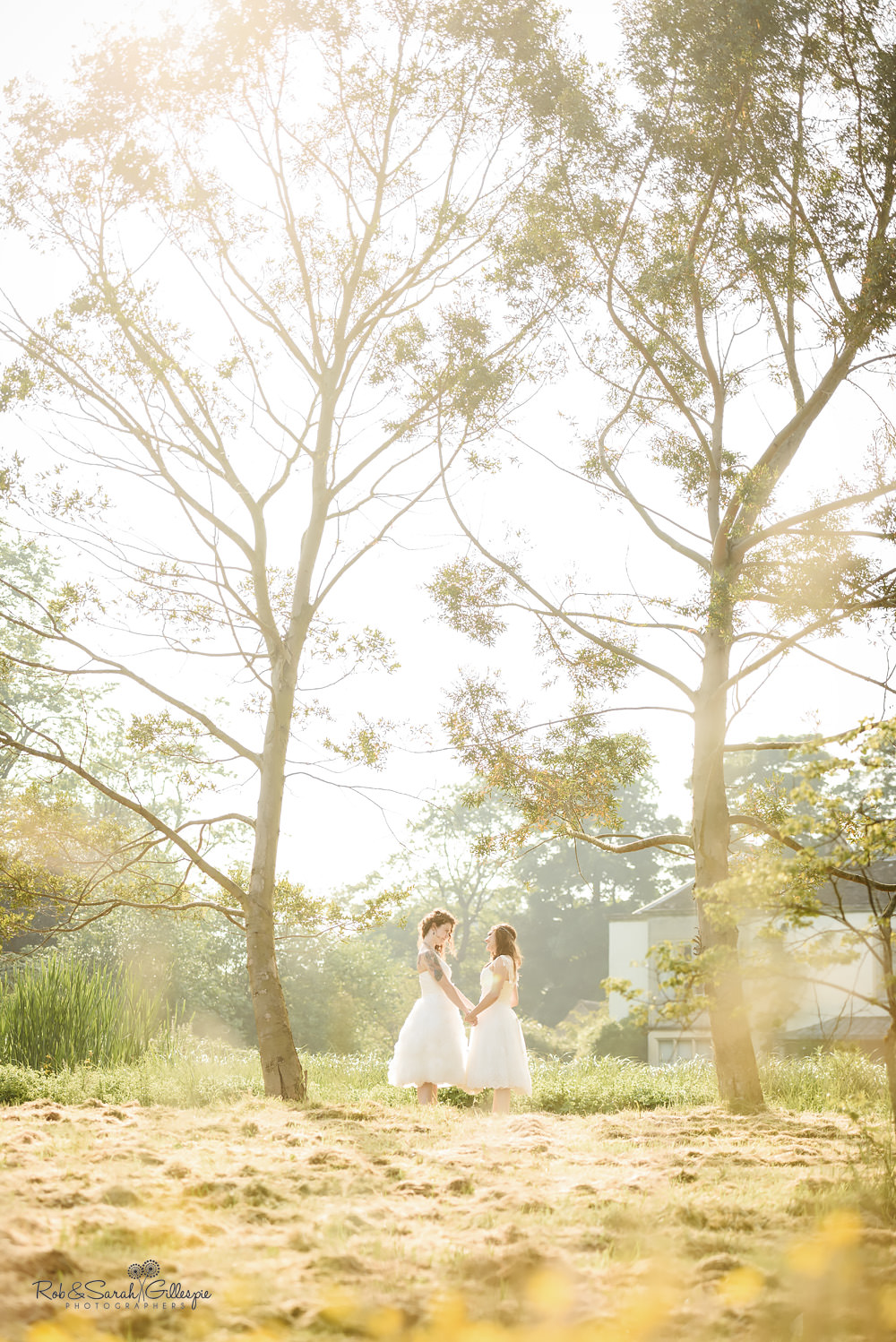 Two brides holding hands between beautiful trees at the Matara Centre