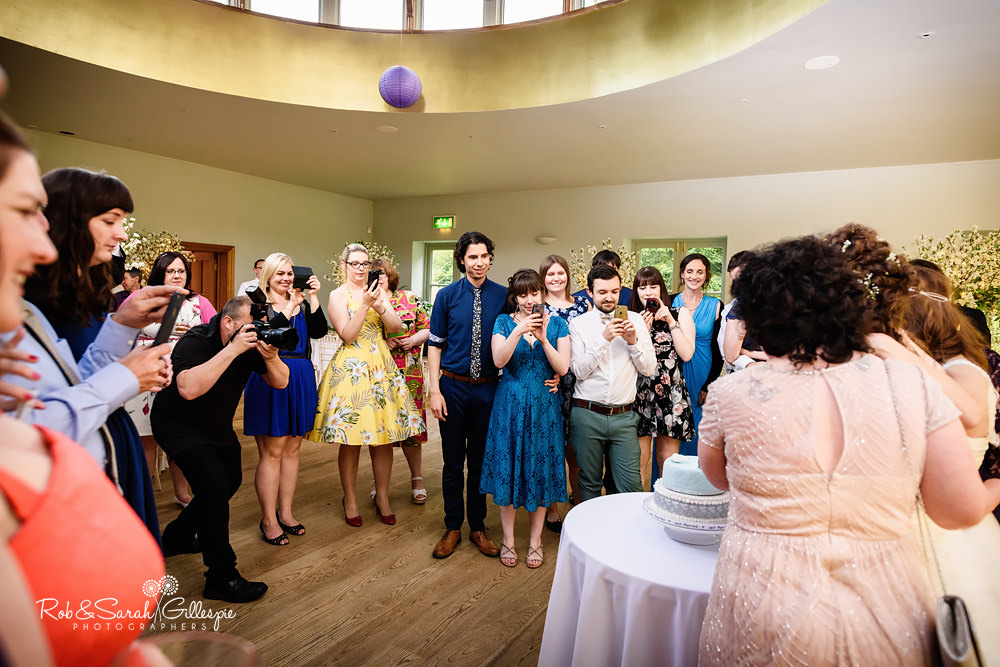 Wedding guests take pictures of brides cutting cake