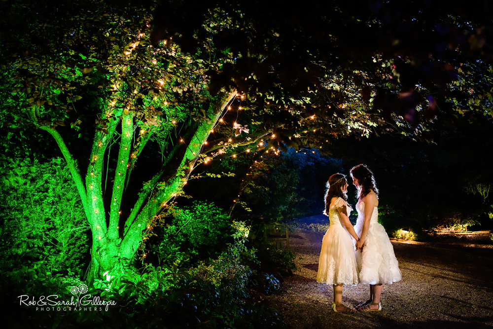 Two brides hold hands next to illuminated tree at night at the Matara Centre