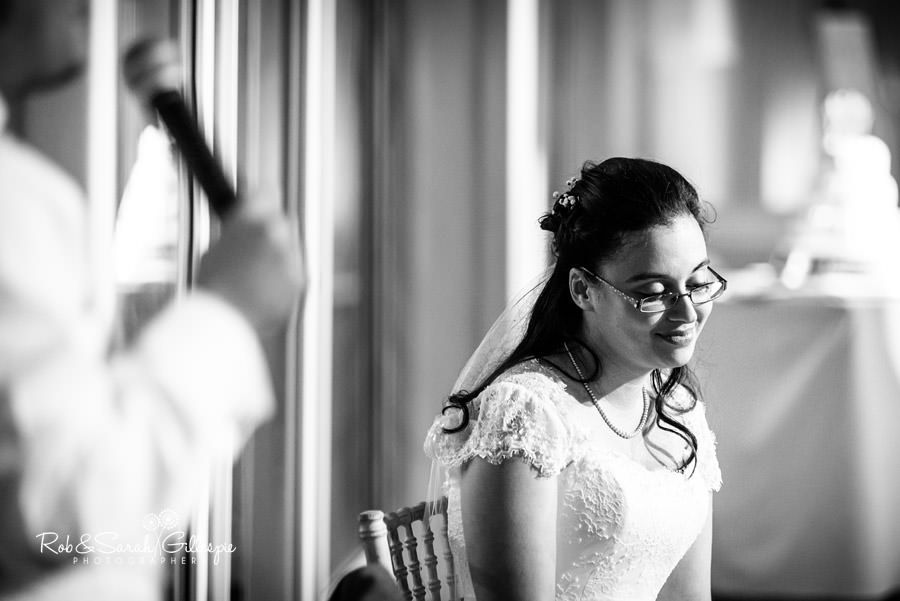 Bride listening to husband give speech.