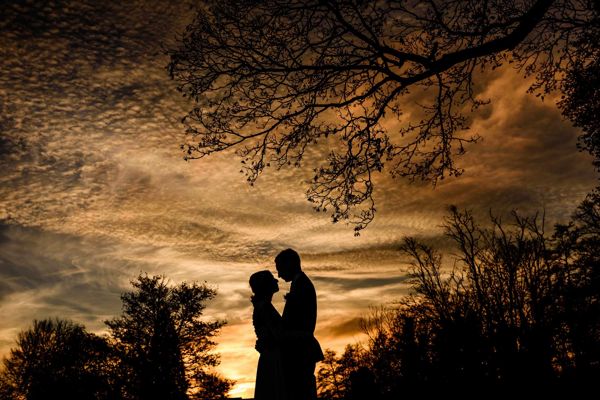 Bride and groom silhouetted against dramatic sunset