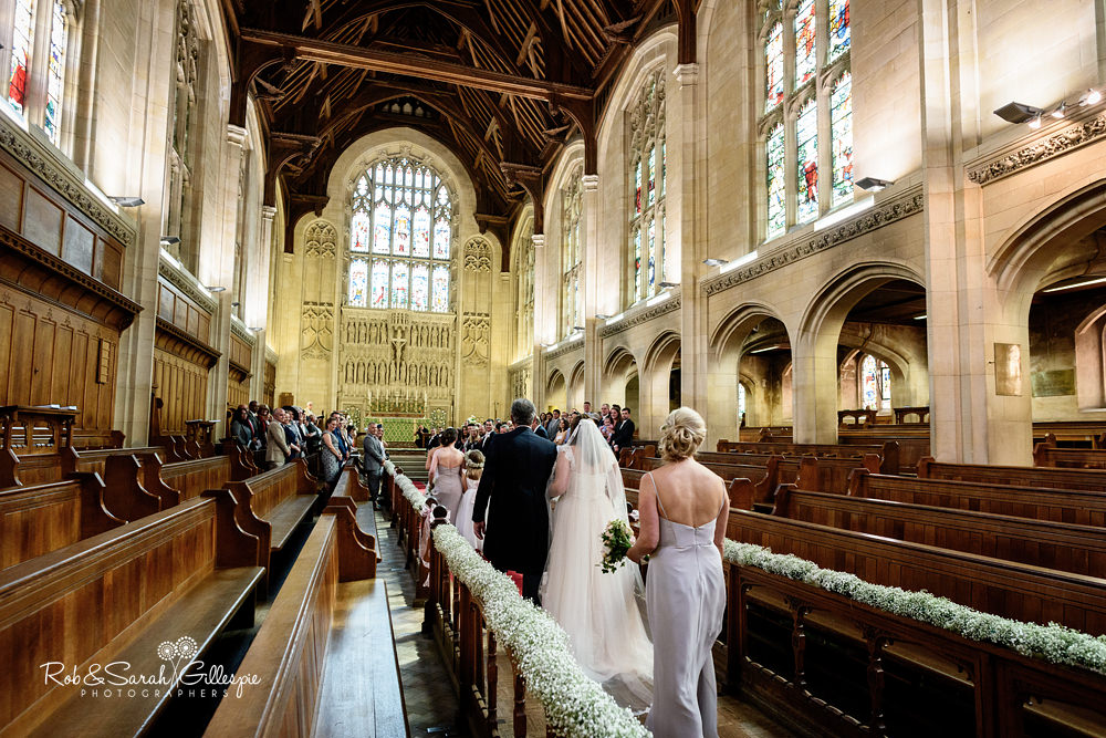 Bride smiling at groom as she walks up the aisle in chapel at Malvern College