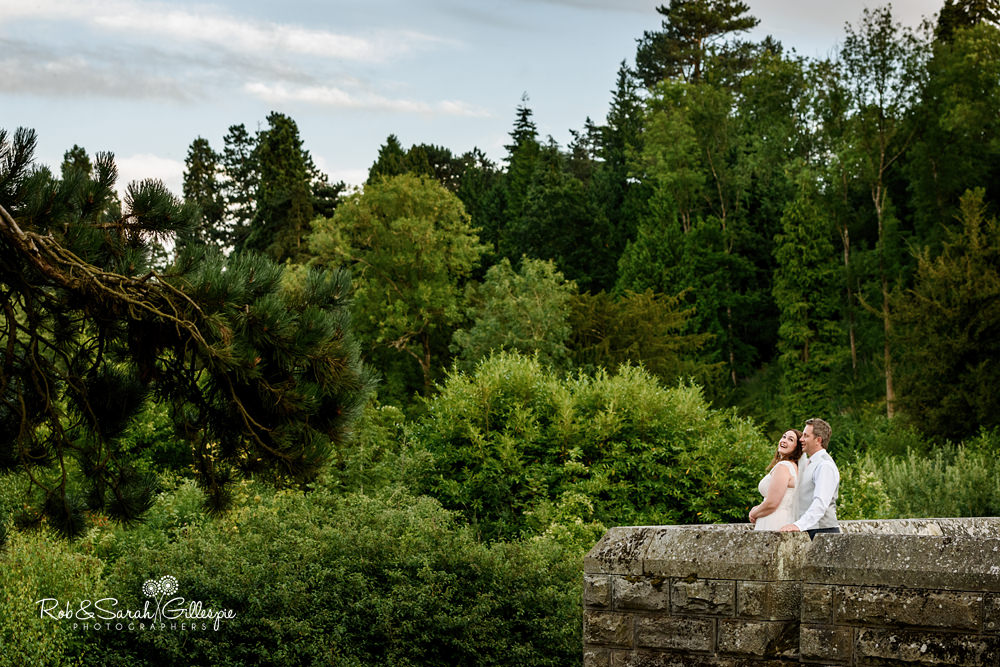 Bride and groom enjoying a moment together in grounds of Eastnor Castle