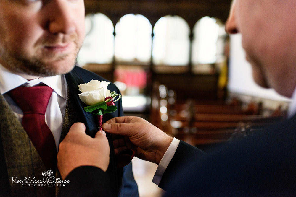 Groom has buttonhole flower fastened at All Saints church Grendon