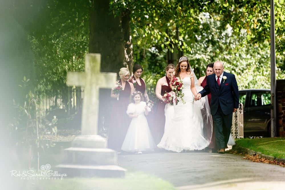 Bride and bridesmaids walk towards All Saints church Grendon