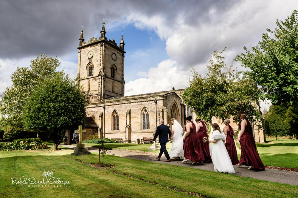 Bride and bridesmaids walk to wedding at All Saints church Grendon