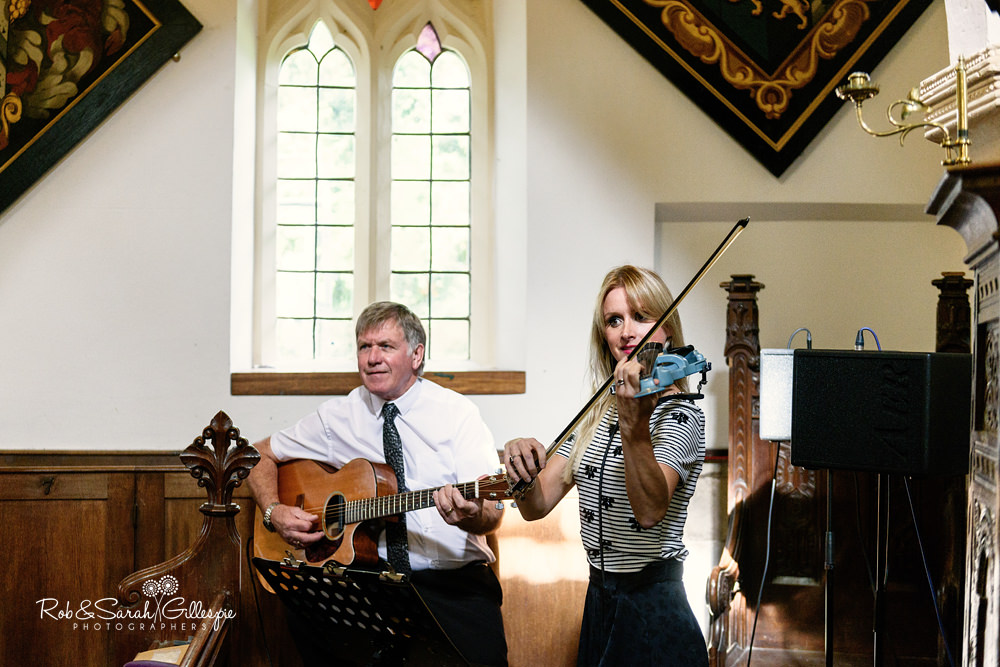 Musicians play inside All Saints church Grendon