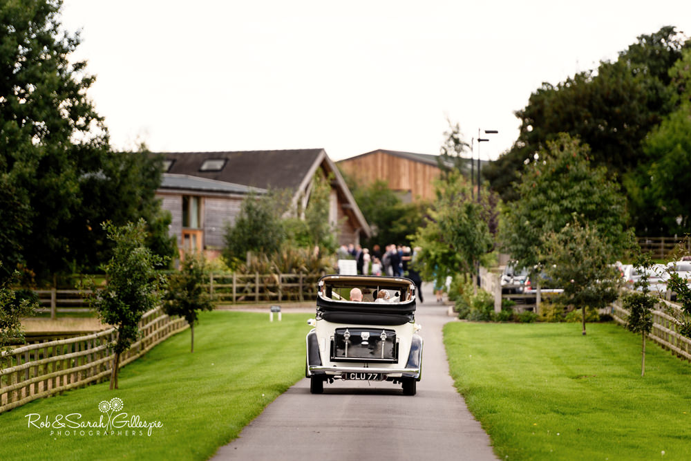 Bride and groom arrive at Mythe Barn wedding reception in open-top car