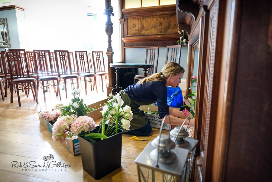 Florist puts finishing touches to flowers in Morning Room at Pendrell Hall