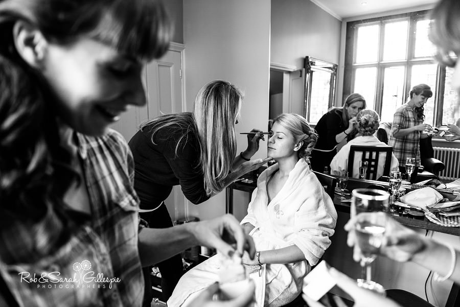 Picture of bride having makeup applied with bridesmaids in foreground