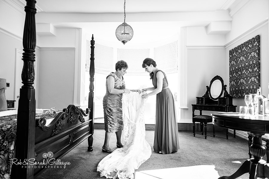 Mother-of-bride and bridesmaid get wedding dress ready for bride