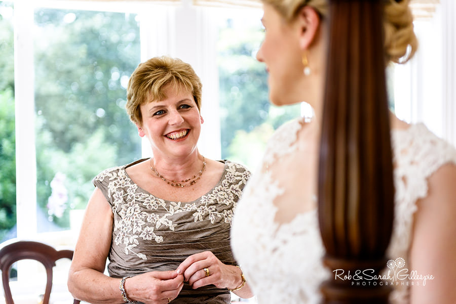 Mother-of-bride smiling at her daughter as she gets ready for wedding