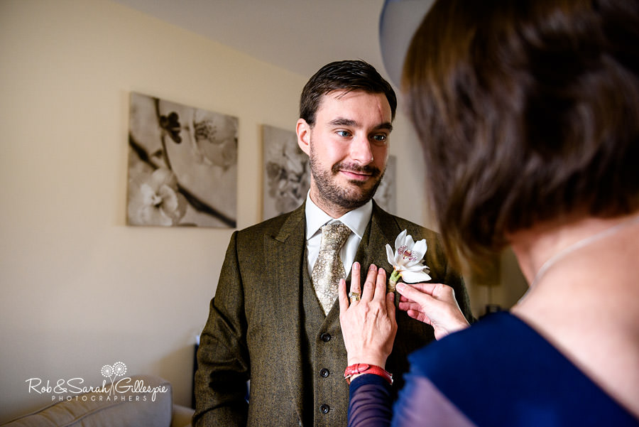 Groom's mother fixes buttonhole flower to suit as groom looks on