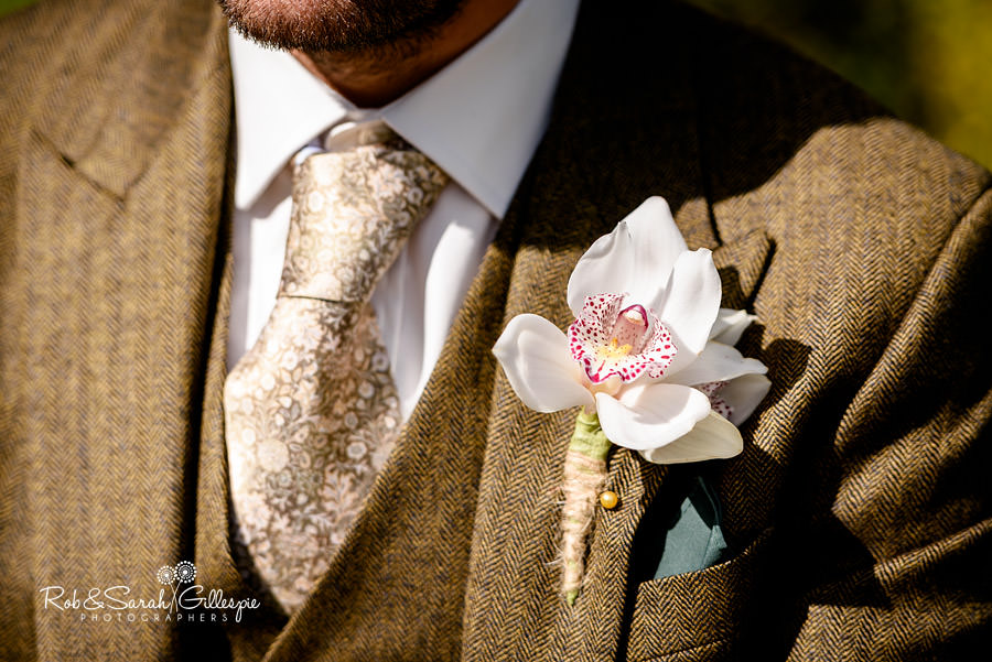 Close-up picture of groom's orchid buttonhole