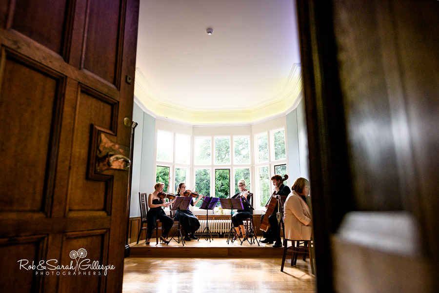 View through doorway into Pendrell Hall Morning Room as string quartet play