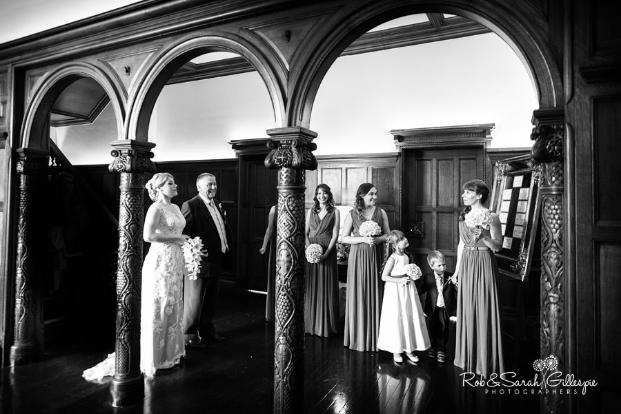 Bride, father and bridesmaids share a moment under archways at Pendrell Hall
