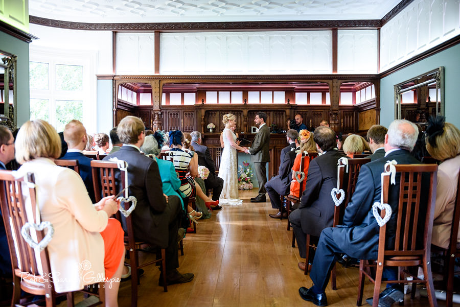 Photo from back of Morning Room at Pendrell Hall as bride and groom face each other to give vows
