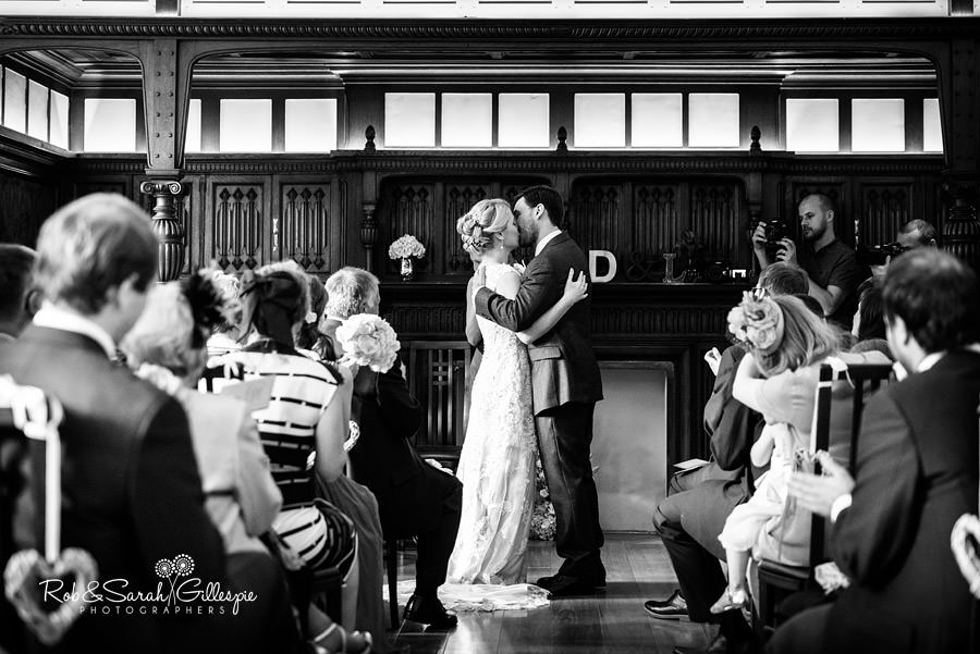 Bride and groom first kiss during wedding service at Pendrell Hall