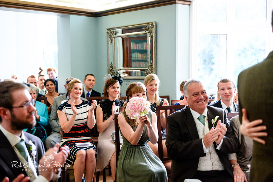 Wedding guests smiling and clapping at end of wedding service