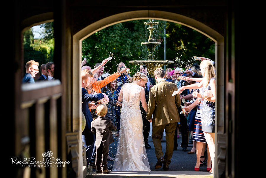 View through Pendrell Hall archway as confetti is thrown over bride and groom in sunshine