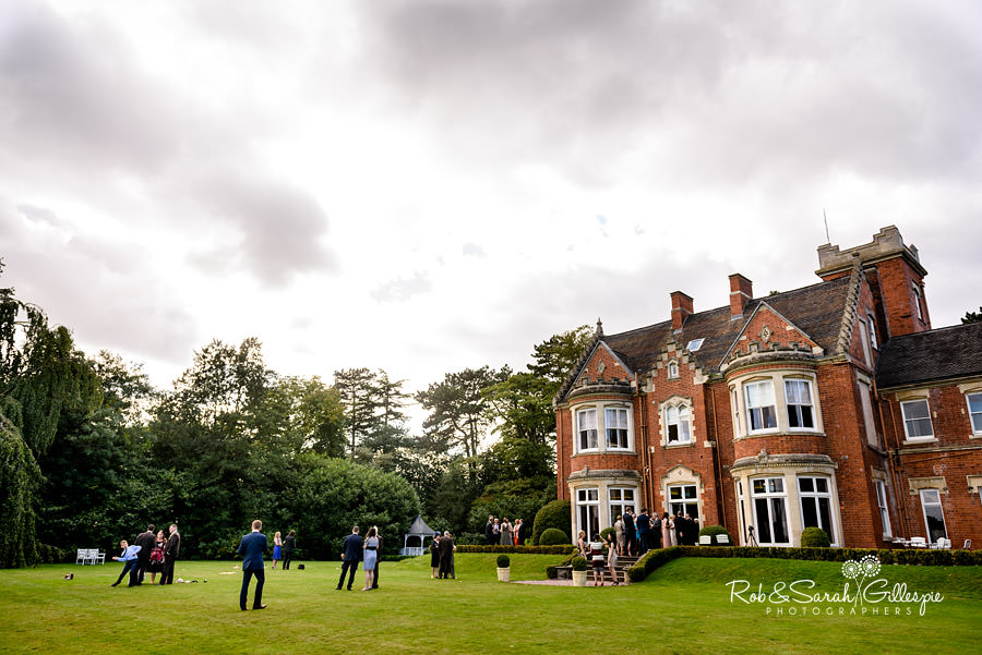 Wide-angle picture of Pendrell Hall grounds with wedding guests enjoying the afternoon