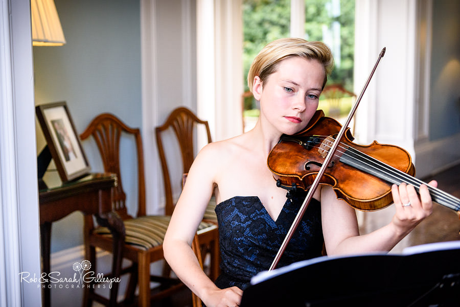 Female violinist plays during drinks reception at Pendrell Hall.