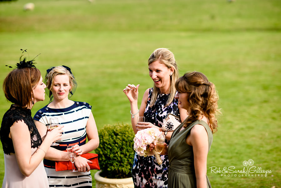 Female wedding guests chat during drinks reception
