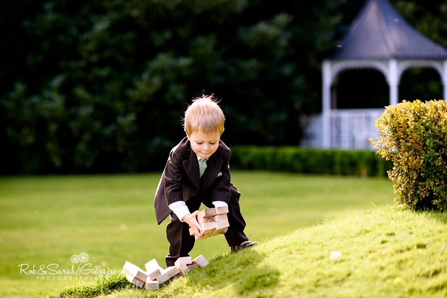 Pageboy plays with Jenga bricks in Pendrell Hall gardens during wedding