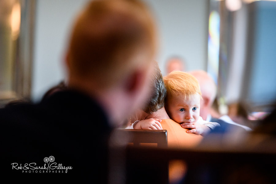 Young boy looks on during wedding speeches