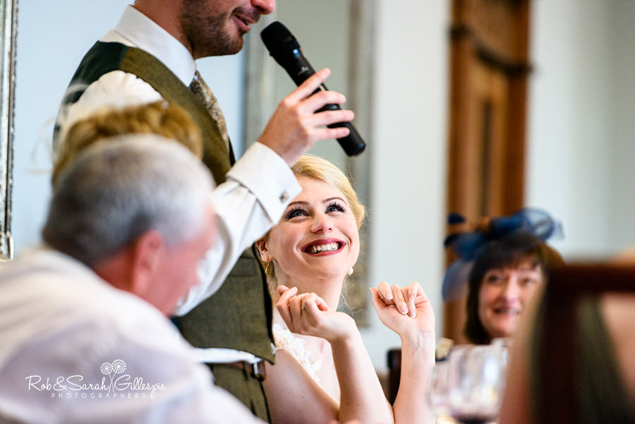 Bride gives huge smile to groom during wedding speech