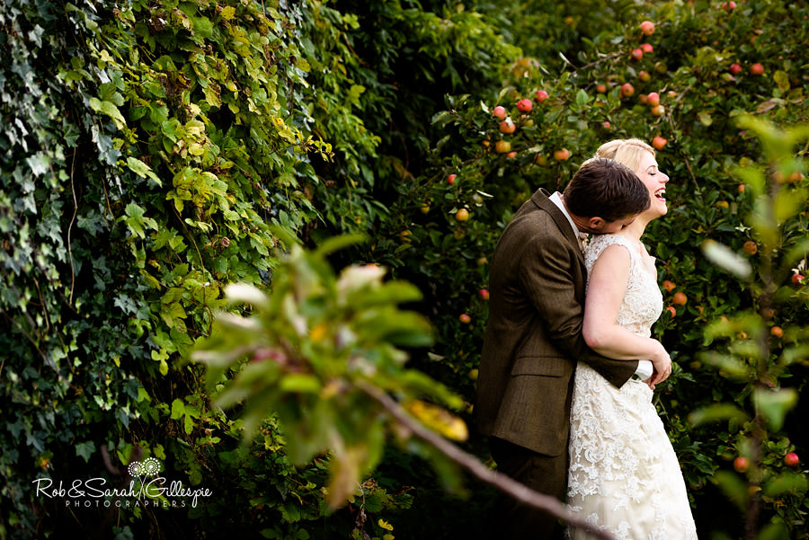 Bride and groom laughing in gardens at Pendrell Hall with apples on the trees behind