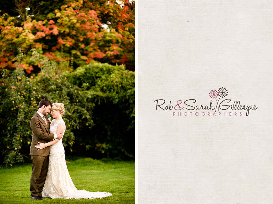 Bride and groom embrace with Autumnal colours on trees in the background