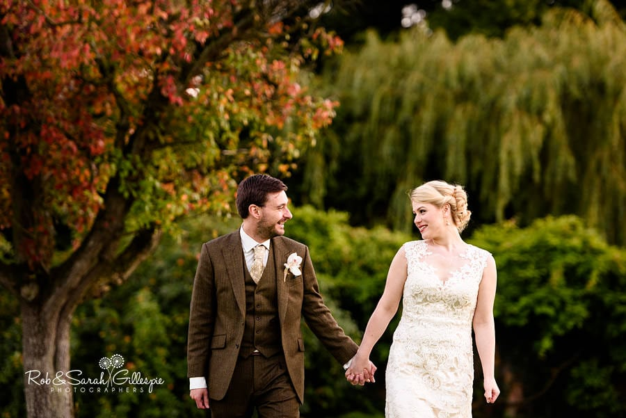 Bride and groom holding hands and walking with Autumn colours in garden