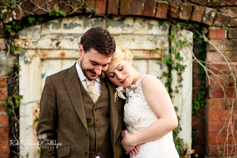 Bride snuggles into groom in front of old garden wall