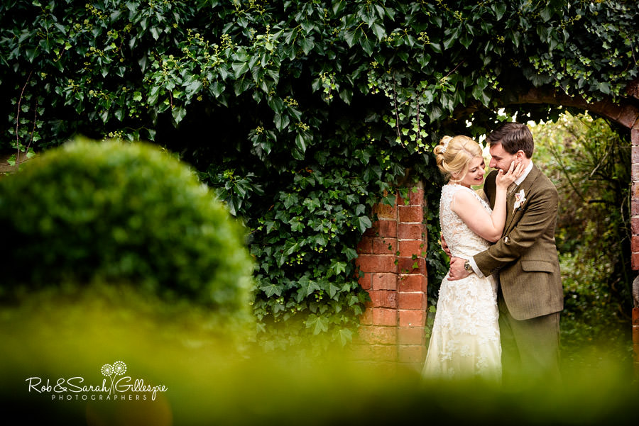 Bride and groom under archway in Pendrell Hall gardens