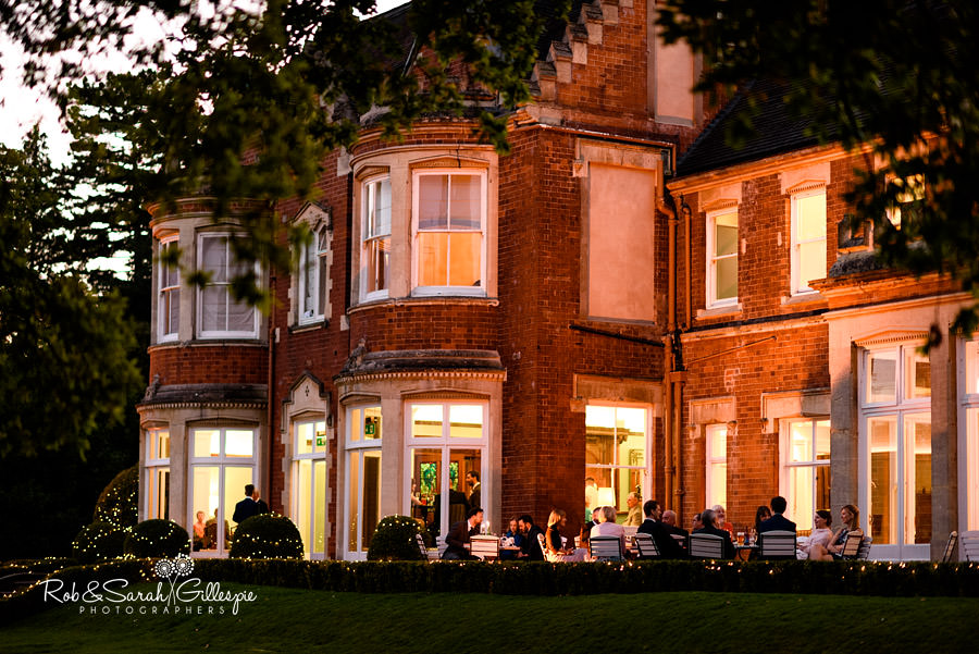 Pendrell hall lit up during evening with guests enjoying drink outside