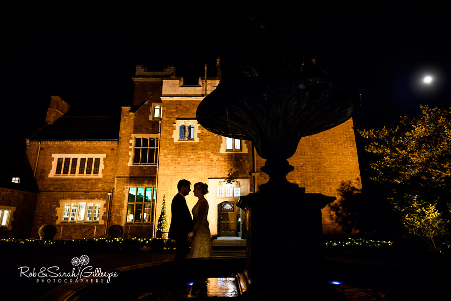 Bride and groom in silhouette in front of Pendrell Hall at night