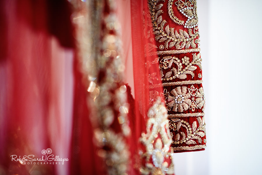 Indian wedding dress detail with gold embroidery on red cloth