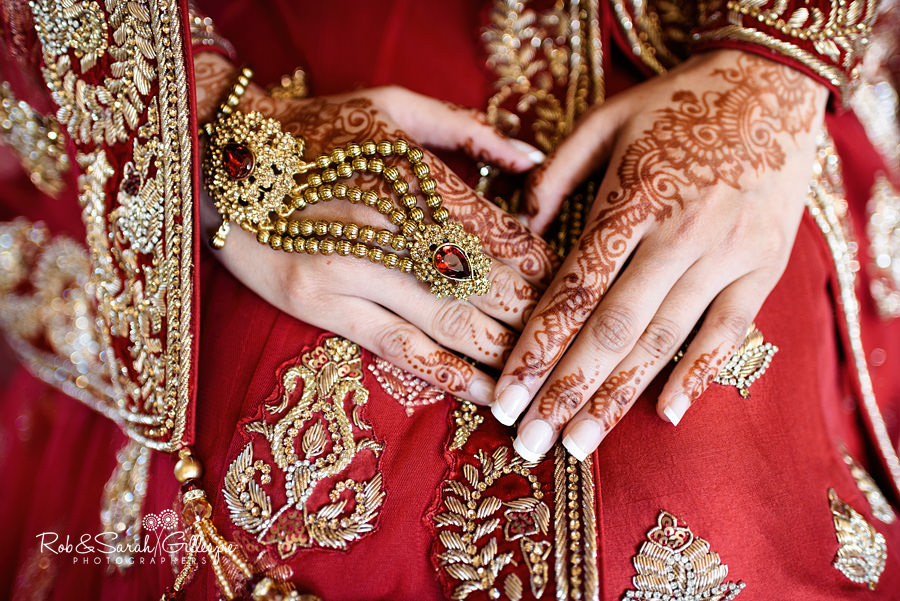Close-up image of bride's hands, with gold jewellery and henna patterns