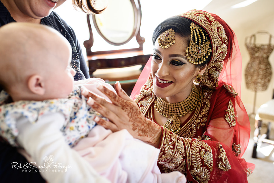 Bride smiling at baby while getting ready for wedding