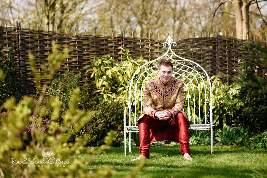 Portrait of groom in traditional Indian wedding costume in gardens at Warwick House