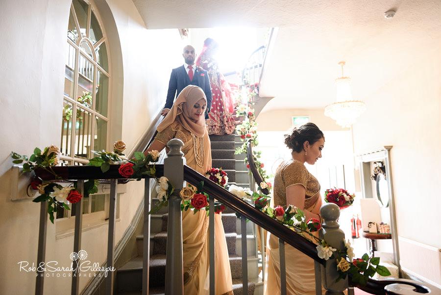Bridesmaids walk down stairway at Warwick House