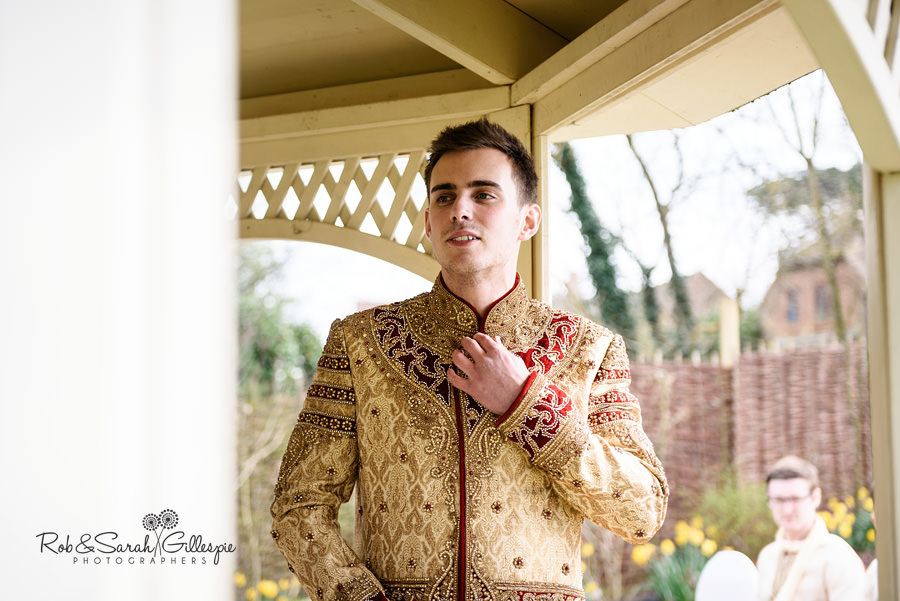 Groom adjusting his outfit before outdoor wedding ceremony at Warwick House